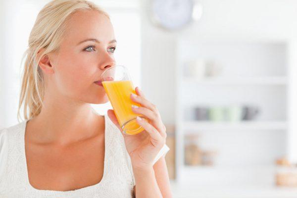 Женщина пьёт свежевыжатый сок