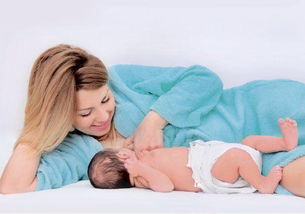 Девушка в голубом халате лежит вместе с малышом в подгузнике