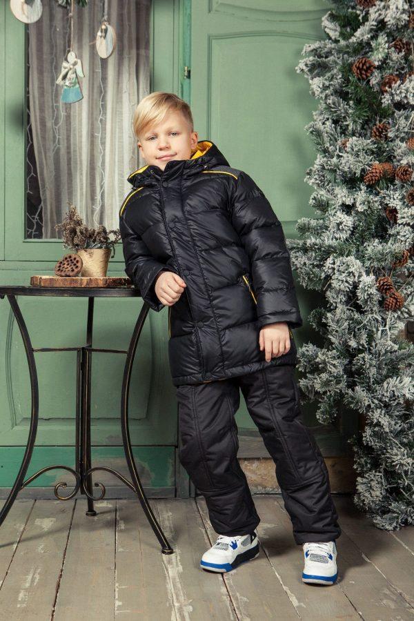 Мальчик в черном пуховике рядом с елкой