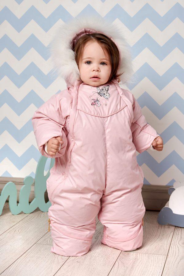 Маленькая девочка в зимнем комбинезоне розового цвета