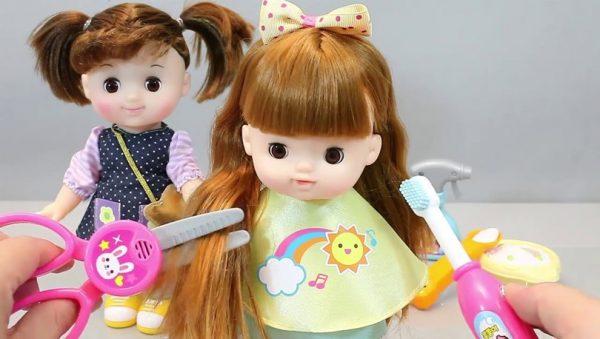 Игрушечными ножницами кукле обрезают волосы