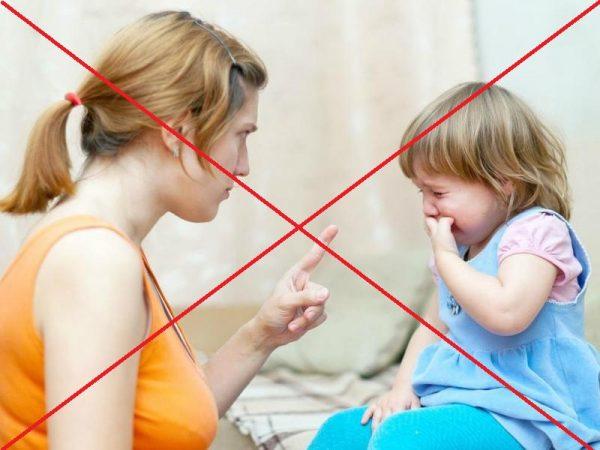 Мама грозит девочке пальцем и строго на неё смотрит