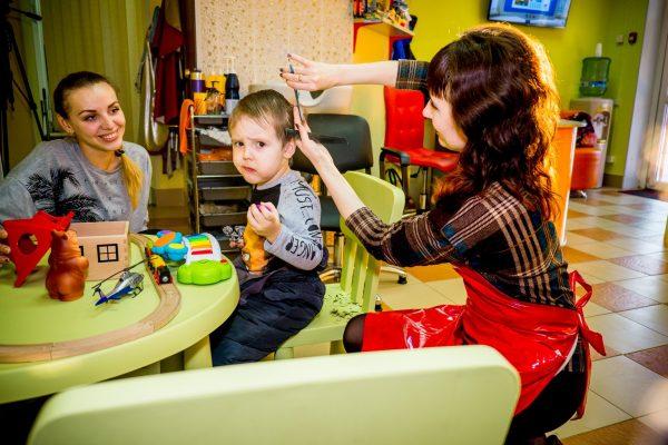 Ребёнок сидит за столом и играет, рядом сидит мама, а парикмахер стрижёт малыша