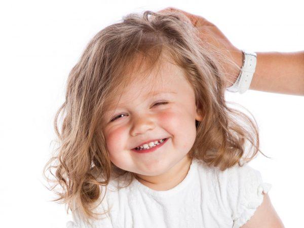 Взрослый человек взъерошивает волосы маленькой девочке