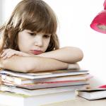 Девочка с грустным видом сидит, положив руки на учебники