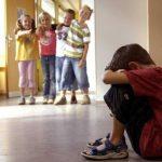 Одноклассники смеются над мальчиком, он сидит на полу, закрыв лицо руками