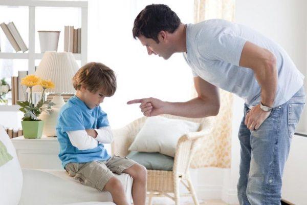 Отец грозит пальцем сыну, мальчик сидит скрестив руки
