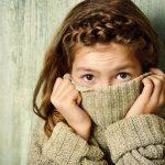 Взволнованная девочка натянула свитер до самых глаз