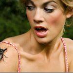 Женщина испугана жуком, который сидит на её плече