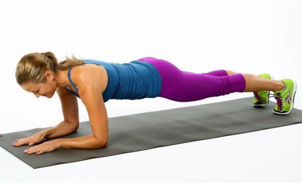 Женщина лицом к полу делает упор на руках и ногах