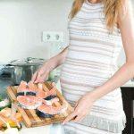 Беременная готовит рыбу