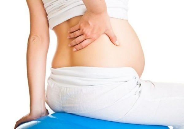 Беременная женщина сидит и держится за почки