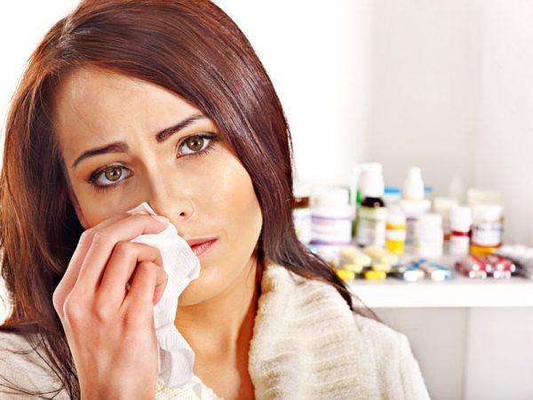 женщины прикладывает платок к области сбоку от носа