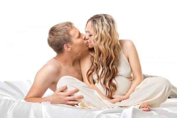 Мужчина и беременная женщина целуются в постели