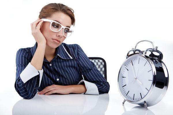 девушка в очках смотрит на настольные часы