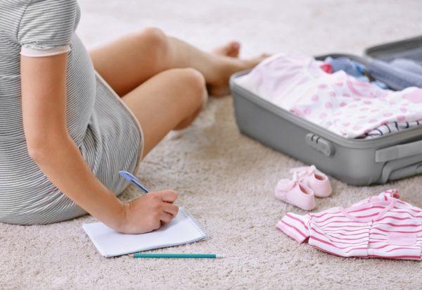 Беременная складывает детские вещи в чемодан