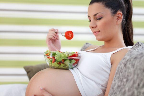 Беременная женщина с тарелкой овощного салата