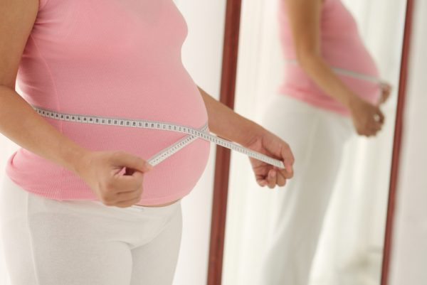 Беременная перед зеркалом измеряет животик сантиметровой лентой