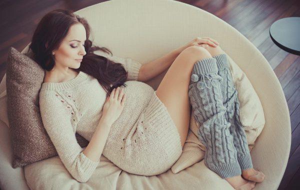 Беременная лежит в круглом кресле и гладит животик