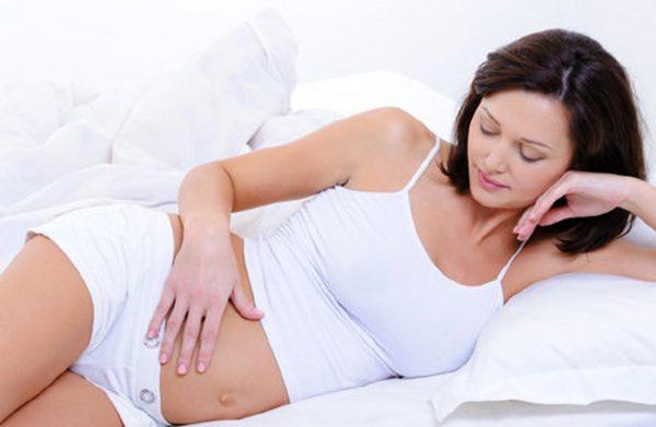 Беременная женщина лежит в постели, держа руку на животе