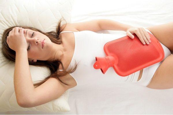 Женщина лежит с грелкой на животе