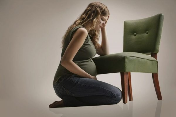 грустная беременная сидит на полу с закрытыми глазами, держась за голову