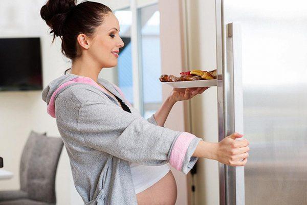 Беременная с тарелкой еды у открытого холодильника