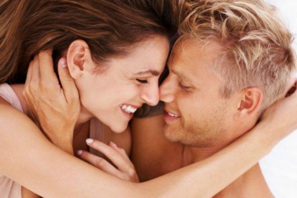Обнимающиеся и улыбающиеся мужчина с женщиной