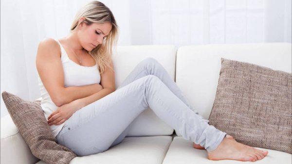 Женщина сидит на диване и обнимает руками живот