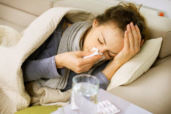 женщина лежит, накрывшись одеялом, держит салфетку у носа