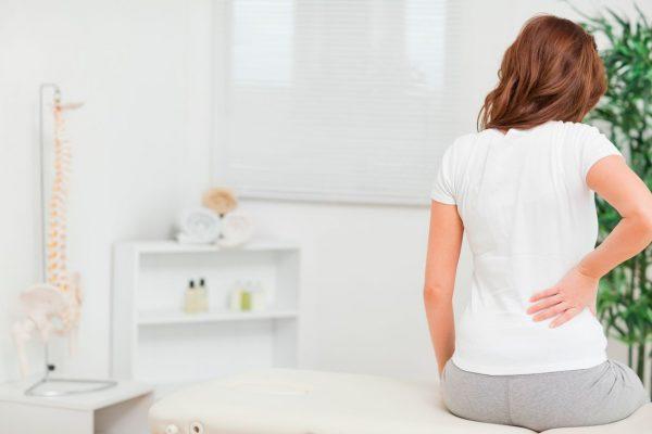Сидящая на кушетке женщина испытывает боль в пояснице