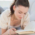 Женщина читает книгу, лёжа на диване