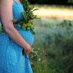 Животик женщины на 27-й неделе беременности, которая гуляет на лугу