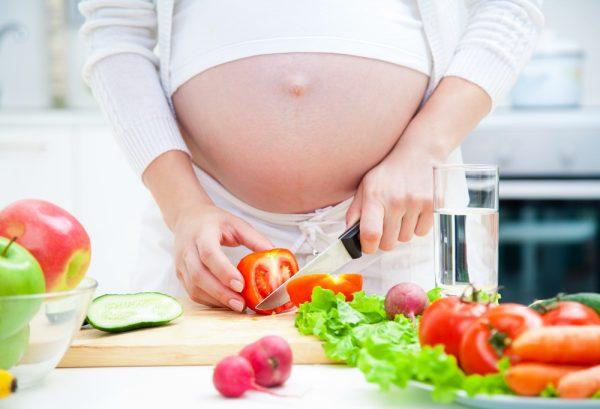 Беременная женщина готовит салат из овощей