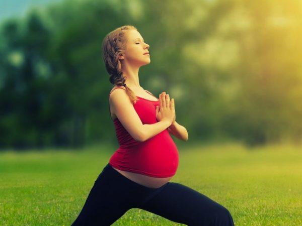 Беременная женщина делает дыхательную гимнастику на свежем воздухе
