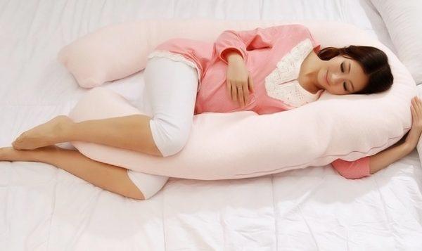 Беременная спит на специальной подушке