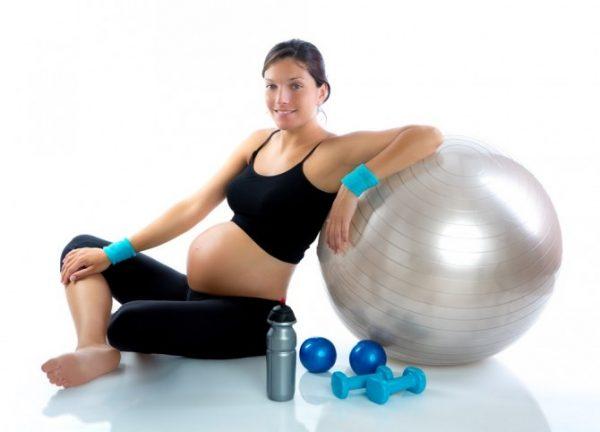 Беременная сидит рядом с гантелями, опираясь на фитбол