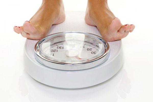 Женщина стоит на напольных весах
