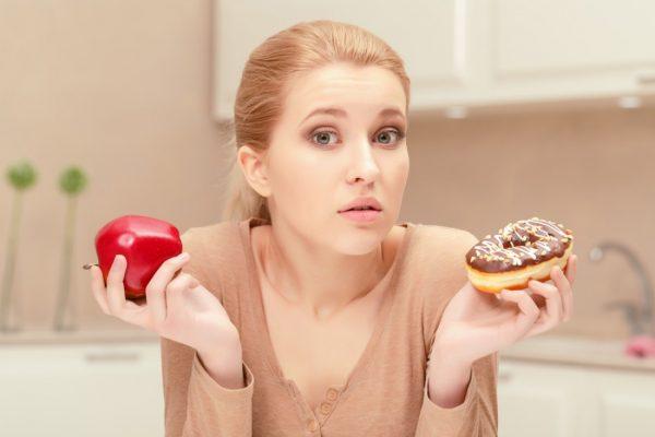 Женщина держит в руках пончик и яблоко