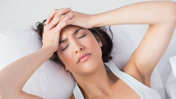 Женщина испытывает боль и двумя руками держится за голову