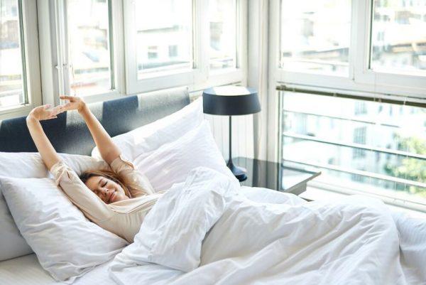 Женщина тянется в постели