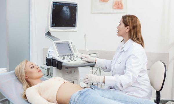 Врач проводит процедуру УЗИ у женщины