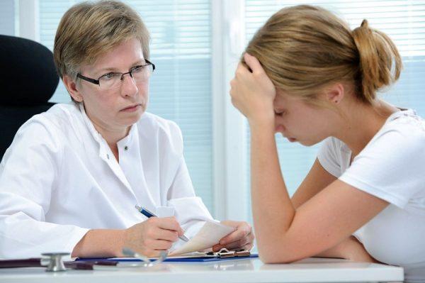 Расстроенная женщина сидит за столом возле врача