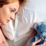 Женщина лежит на кровати с грустью смотри на плюшевого мишку