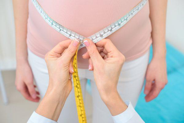 Измеряют живот сантиметровой лентой