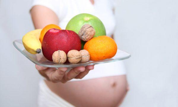 Беременная женщина с тарелкой фруктов