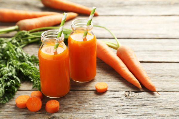 Морковь и баночки с морковным соком на столе