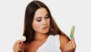 Брюнетка с таблетками в руках и прикушенной губой
