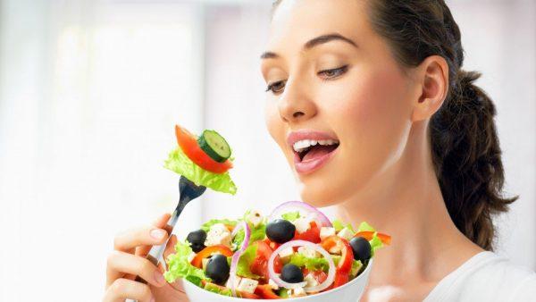 Женщина наслаждется овощным салатом