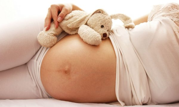 Оголённый животик беременной женщины, лежащей на боку с игрушкой